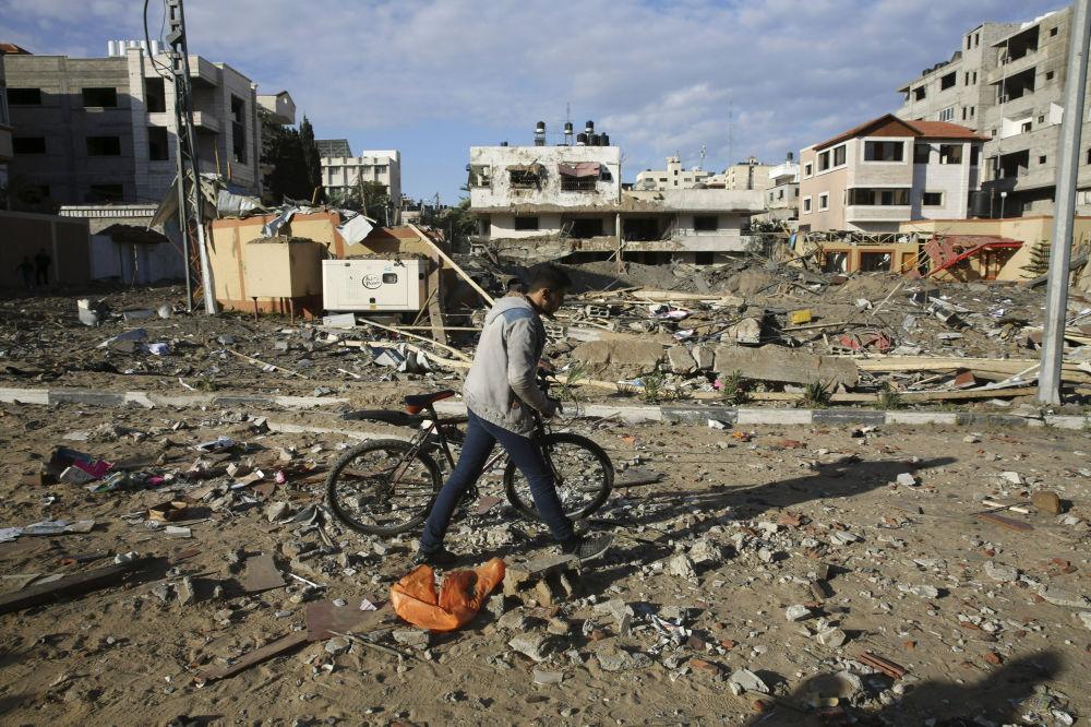 Mieszkaniec Strefy Gazy obok zburzonego budynku Hamasu po izraelskim ataku