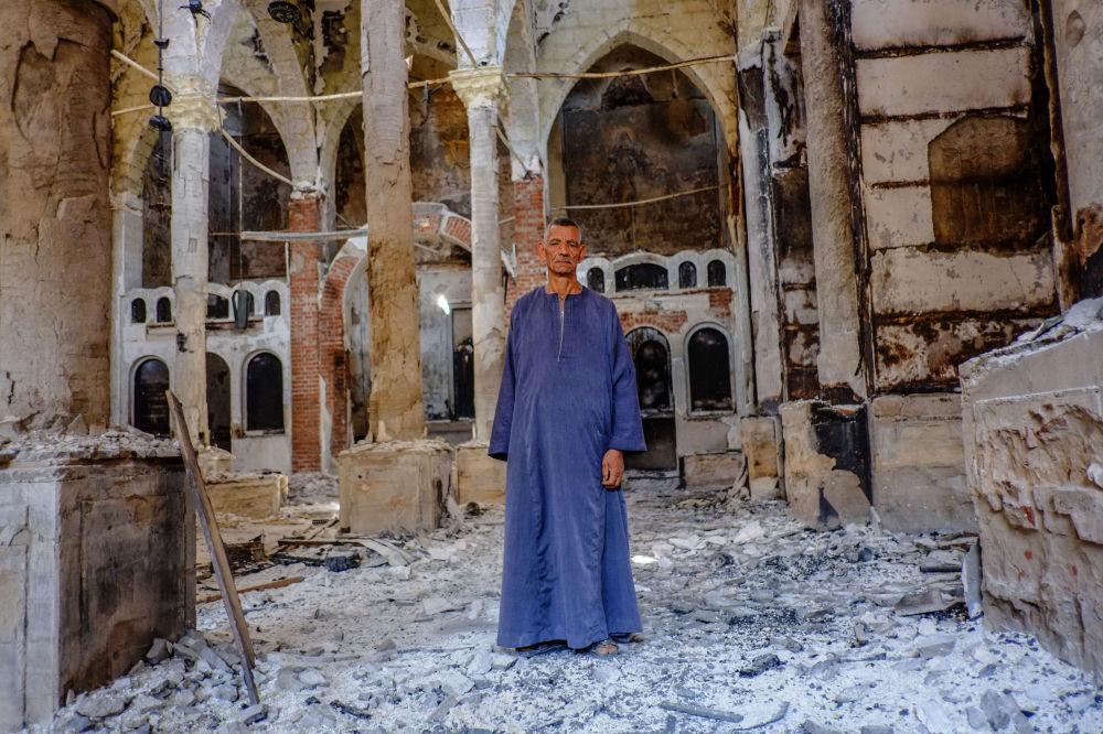 Kopt w jednym ze spalonych i zniszczonych kościołów koptyjskich w prowincji Al-Minja
