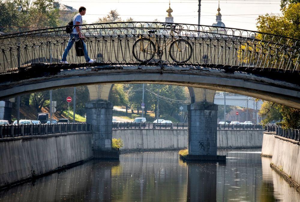 Mężczyzna przechodzi przez most nad rzeką Jauzą w Moskwie