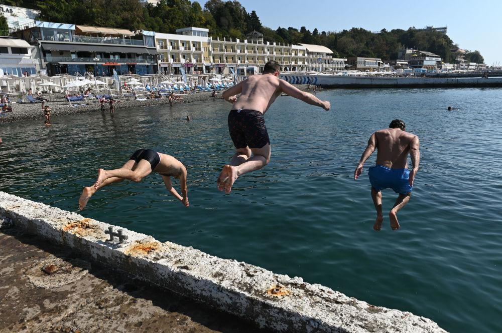 """Mężczyźni skaczą z molo na plaży """"Primorskij"""" w centralnej części miasta Soczi"""
