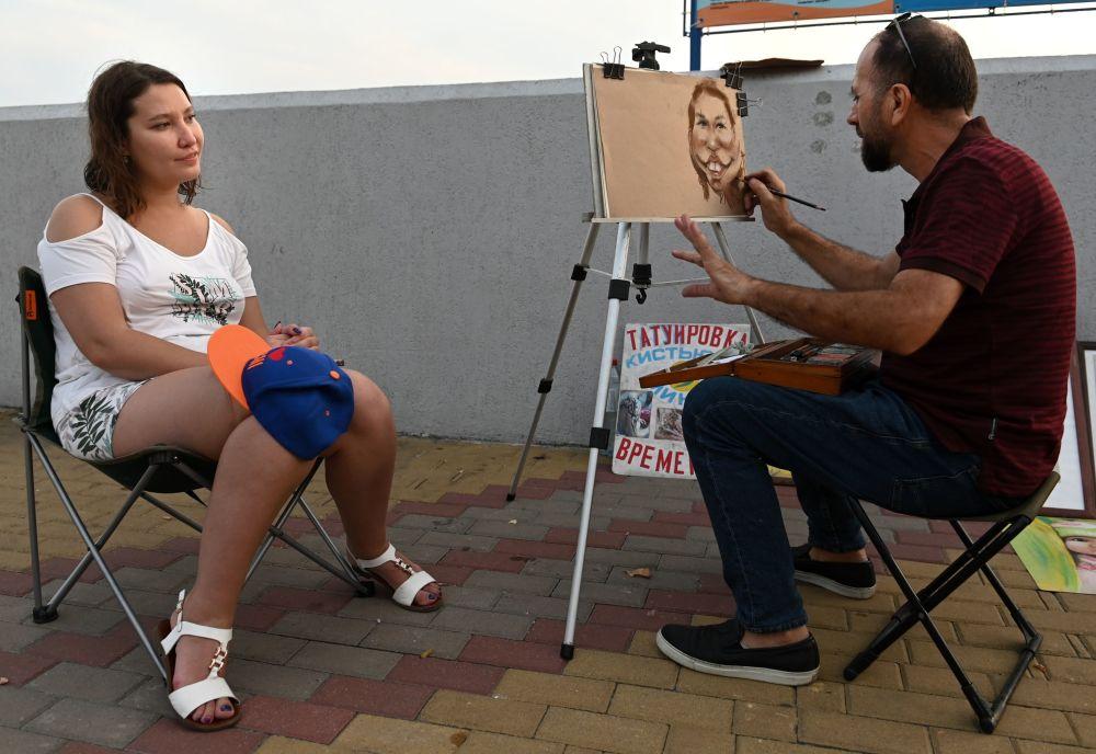 Artysta maluje portret na nasypie w Zatoce Niżhneimeretinskaja w Soczi