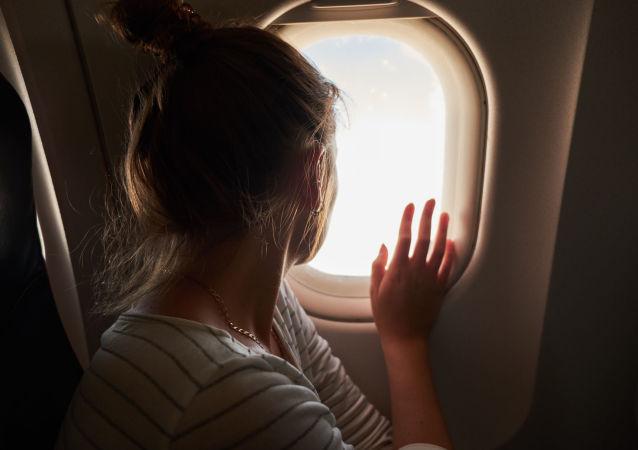 Kobieta wygląda przez okno w samolocie