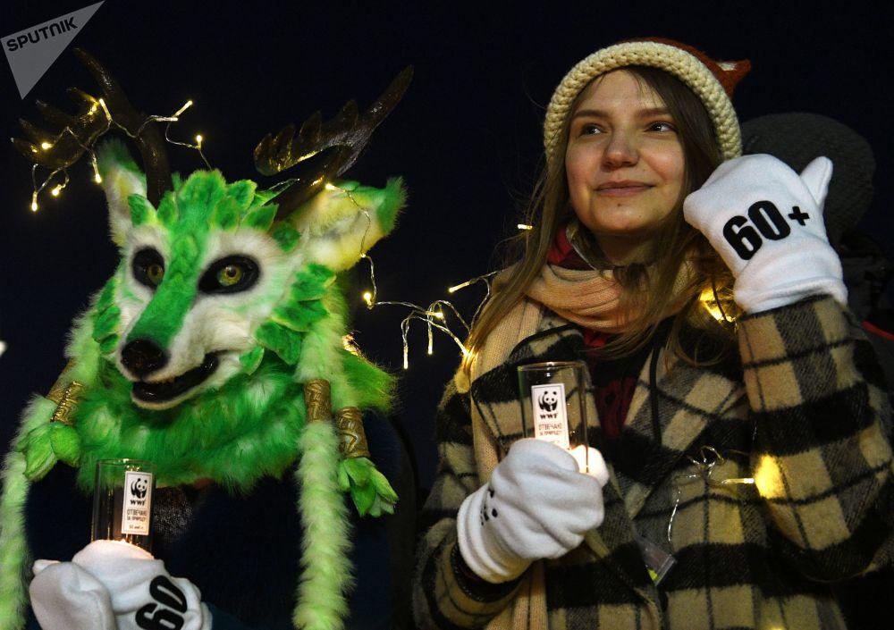"""Uczestnicy akcji ekologicznej """"Godzina dla Ziemi"""" na Placu Czerwonym w Moskwie."""