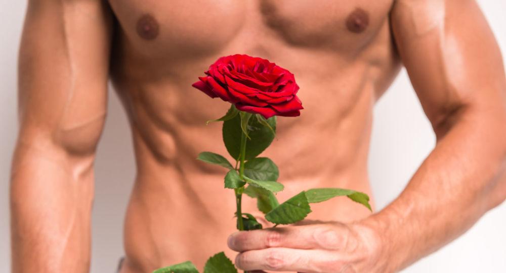 Na pół obnażony mężczyzna z różą w ręku