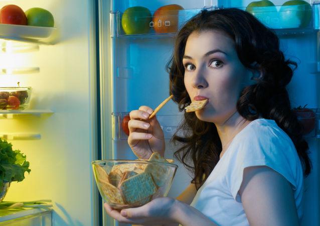 Głodna kobieta przy otwartej lodówce