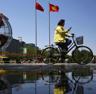 Kobieta na rowerze na placu przed bankiem w Pekinie