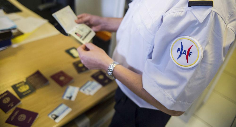 Oficer francuskiej policji przegląda fałszywe paszporty