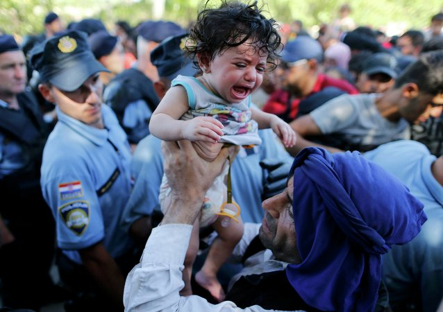 A migrant lifts a crying baby as he waits to board a bus in Tovarnik, Croatia, September 17, 2015