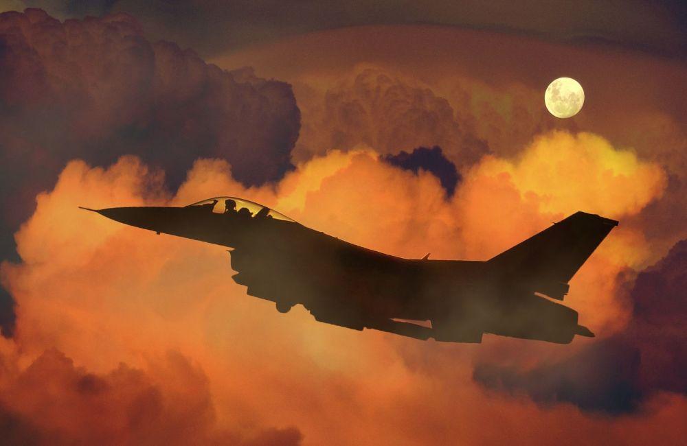 Myśliwiec na tle księżyca i chmur.