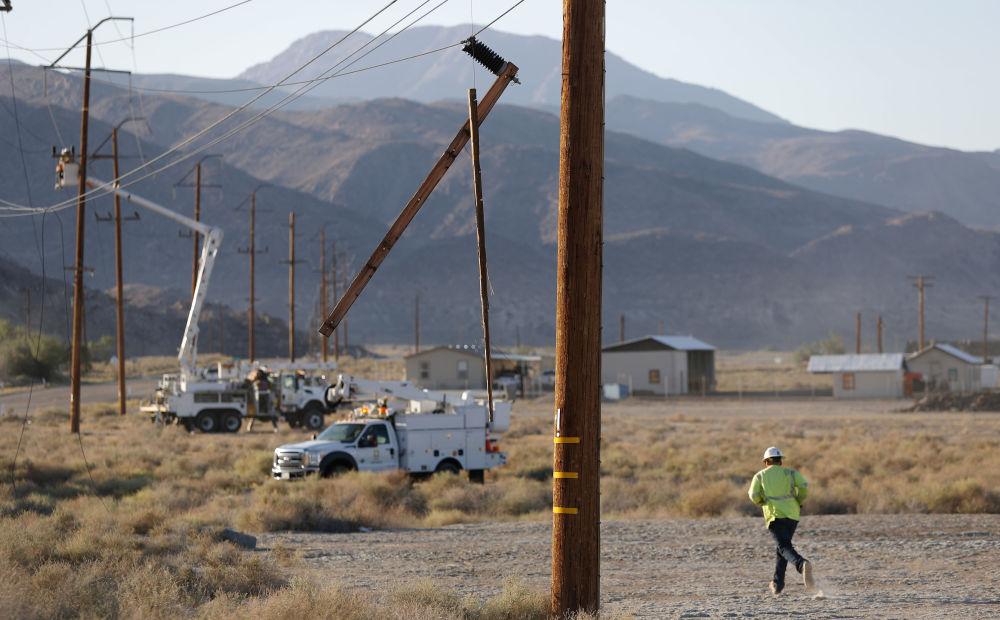Robotnicy naprawiają słupy elektryczne.