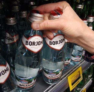"""Kupujący bierze wodę mineralną """"Borjomi"""" z półki w supermarkecie"""