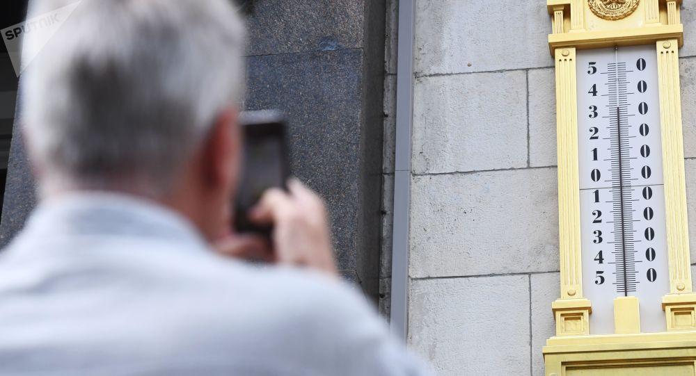 Mężczyzna fotografuje termometr na budynku Dumy Państwowej w Moskwie
