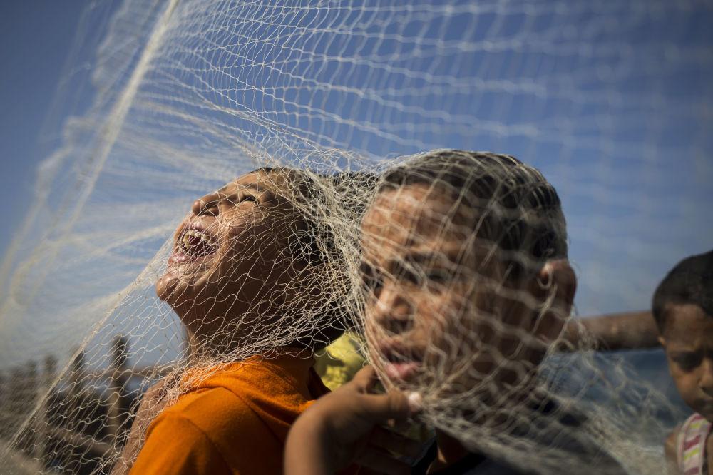 Palestyńscy chłopaki grają z siecią rybacką na brzegu Strefy Gazy