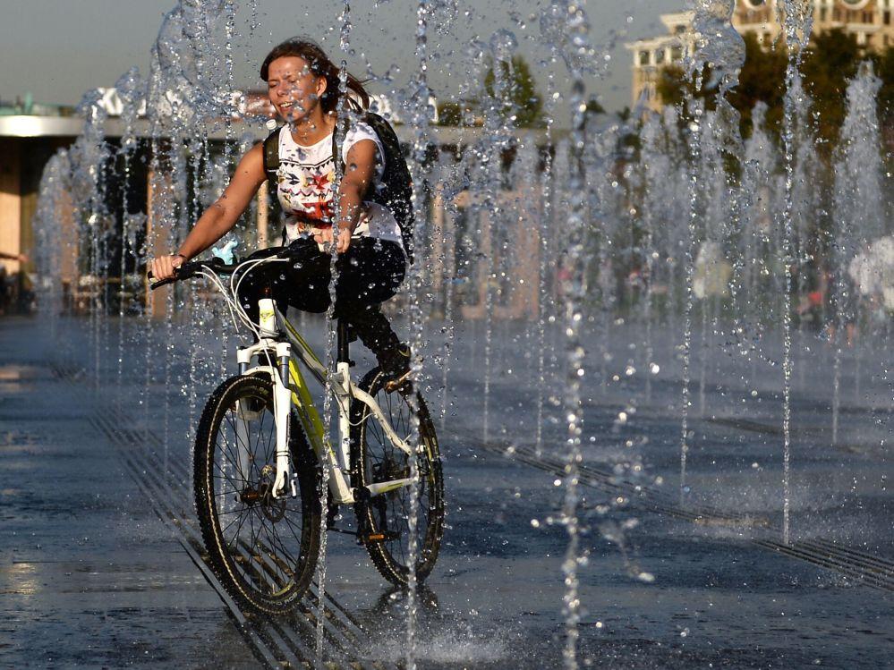 Dziewczyna jedzie na rowerze w parku Muzeon w Moskwie