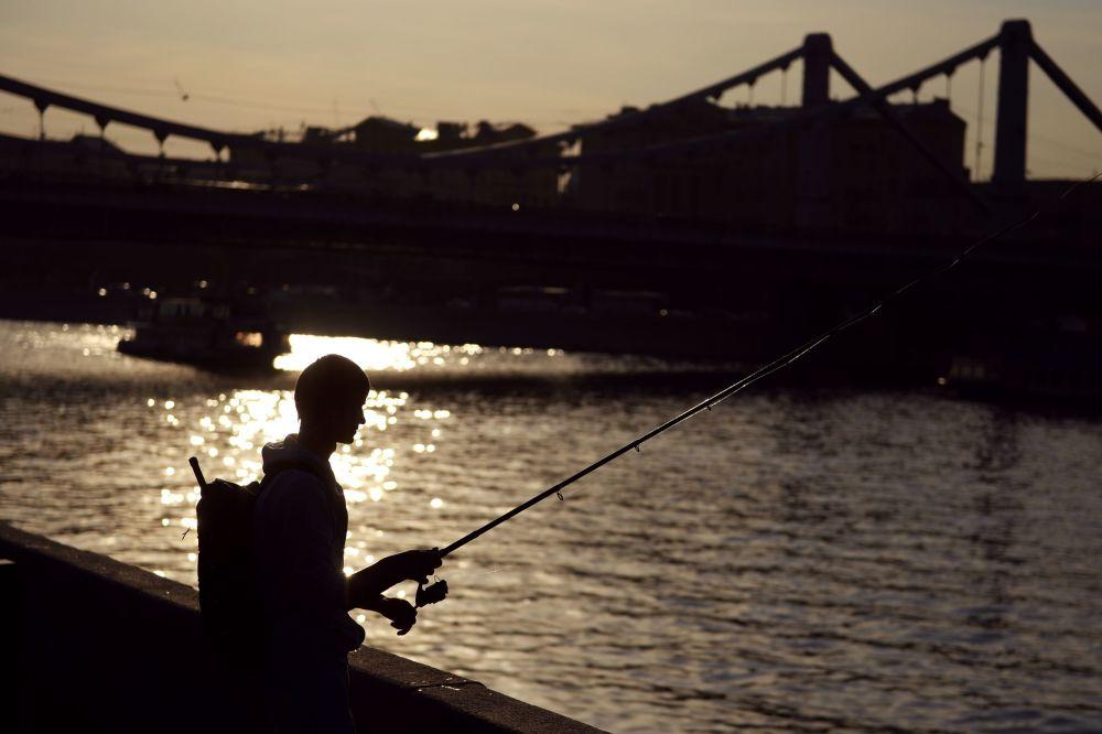 Chłopak łowi ryby na nabrzeżu Moskwy