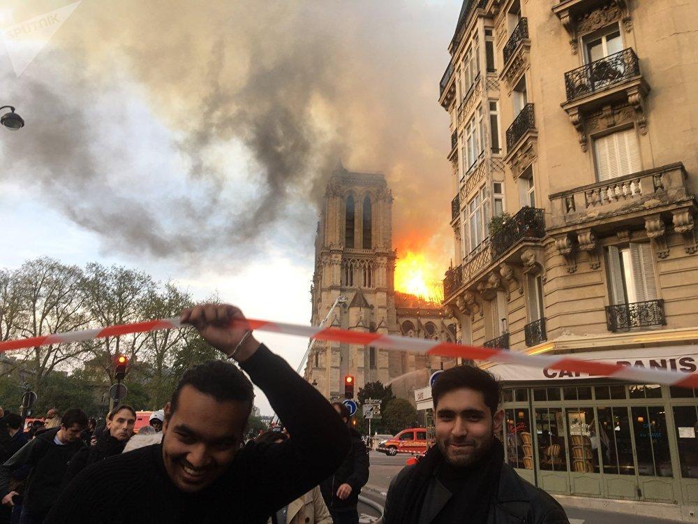 Uśmiechnięci młodzi ludzie w tle płonącej katedry Notre Dame.