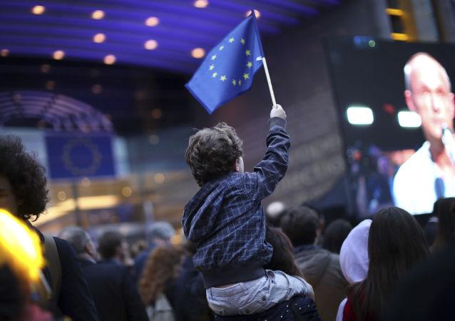 Chłopiec z flagą UE pod budynkiem Parlamentu Europejskiego w Brukseli