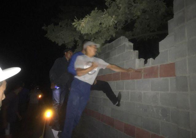 Ludzie przeskakują mur w miejscu zatrzymania byłego prezydenta Kirgistanu Ałmazbeka Atambajewa