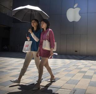 Dziewczyny przechodzą obok sklepu Apple w jednym z centrów handlowych w Pekinie