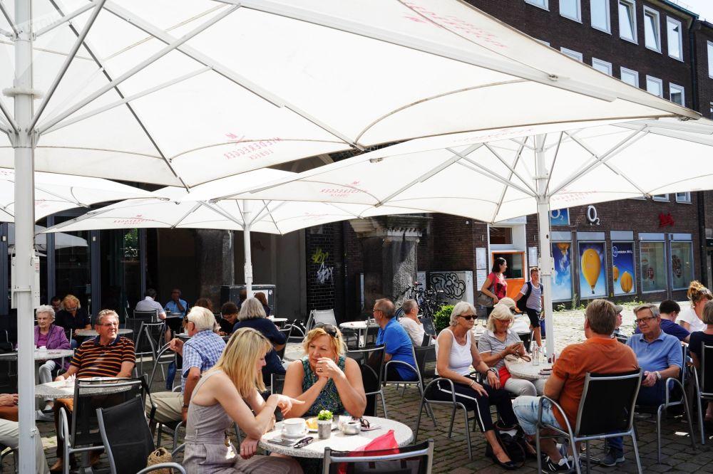 Odwiedzający letnią kawiarnię na jednej z ulic Lubeki.
