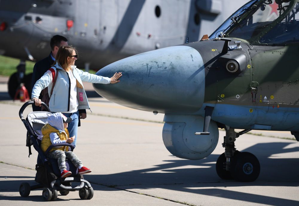 Para z dzieckiem przy śmigłowcu Ka-52 Alligator na Salonie Lotniczym i Kosmicznym MAKS 2019