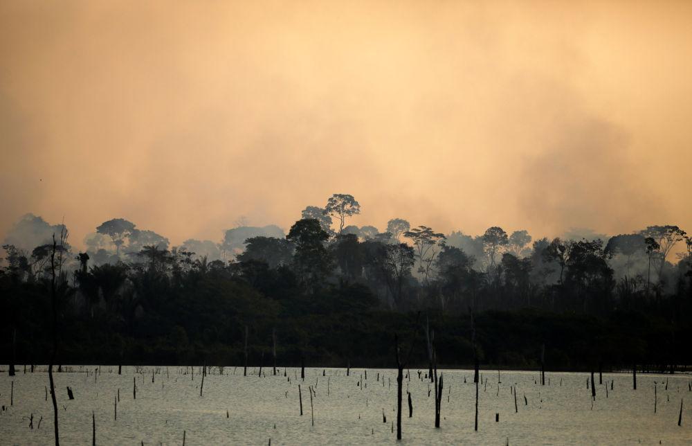 Dym unosi się nad płonącym lasem amazońskim w pobliżu rzeki w Itapuã do Oeste, Rondonia, Brazylia.