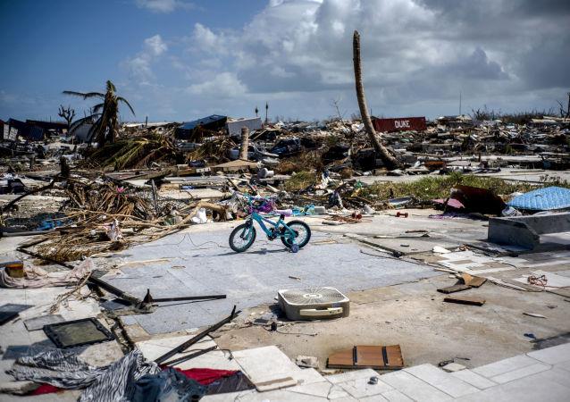 Rowerek dziecięcy na tle zniszczeń po huraganie Dorian w Abaco na Bahamach