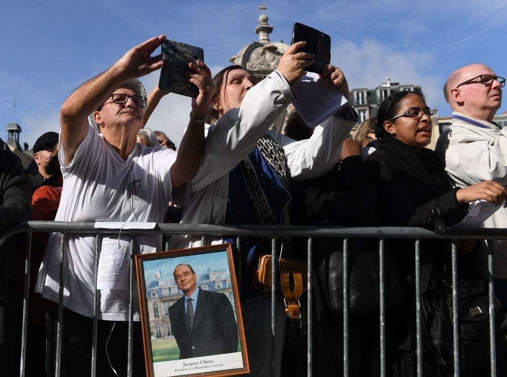 Ludzie zgromadzeni przed kościołem przed ceremonią pogrzebową dla byłego prezydenta Francji Jacquesa Chiraca