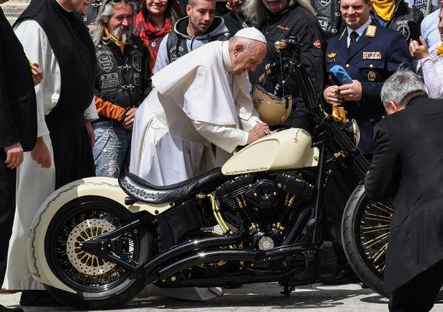 Papież Franciszek składa podpis na motocyklu Harley-Davidson