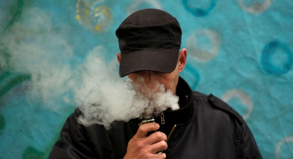 Mężczyzna pali elektronicznego papierosa