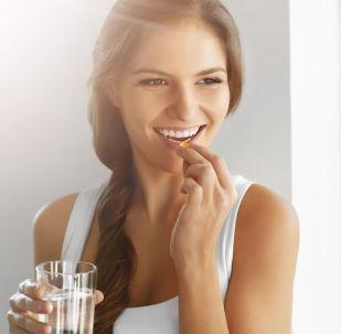 Kobieta ze szklanką wody i kapsułką