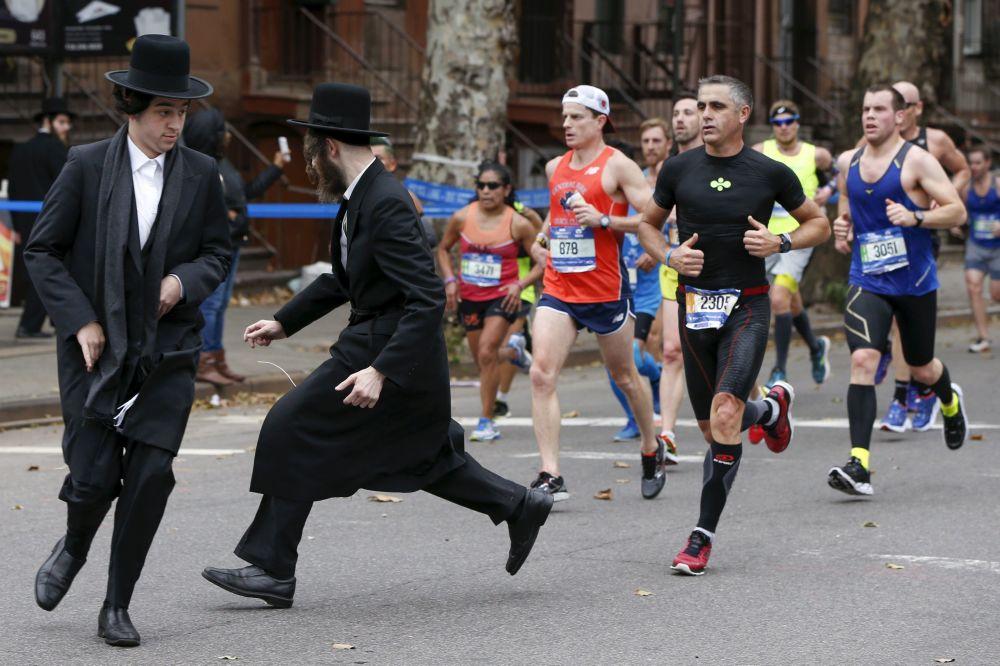 Dwaj Żydzi starają się przebiec przez ulicę przed maratończykami