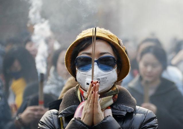 Kobieta w masce świętuje obchody chińskiego nowego roku