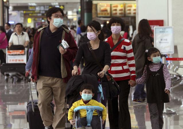 Turyści w maskach na lotnisku Song Shan w Tajpeju