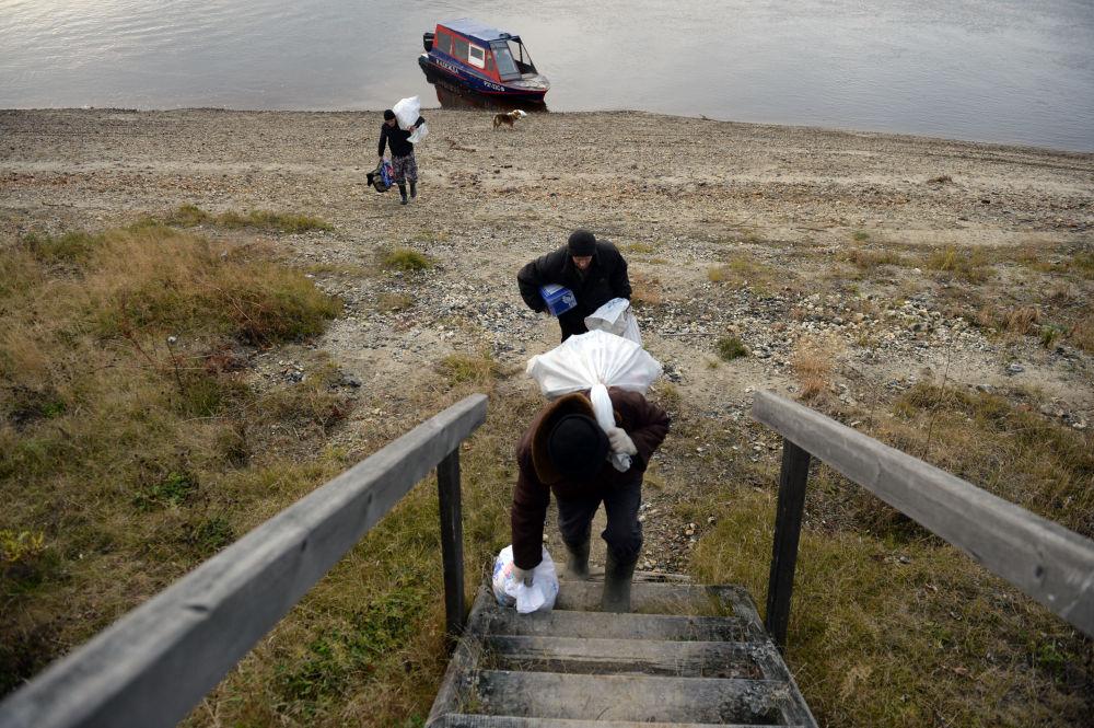 Mieszkańcy miejscowości Szaburowo w obwodzie swierdłowskim pomagają pracownikom poczty wyładować kuter pocztowy