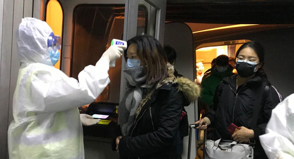 Pracownicy medyczni w kombinezonach ochronnych sprawdzają temperaturę ciała pasażerów przylatujących z Wuhan do Pekinu