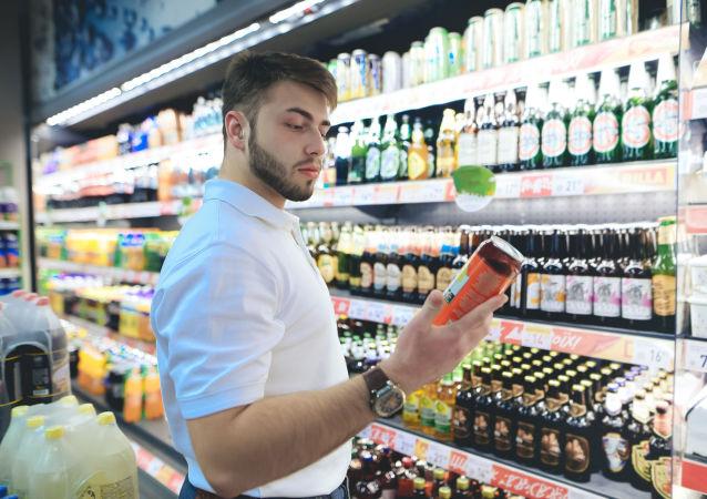 Młody mężczyzna wybiera piwo w sklepie