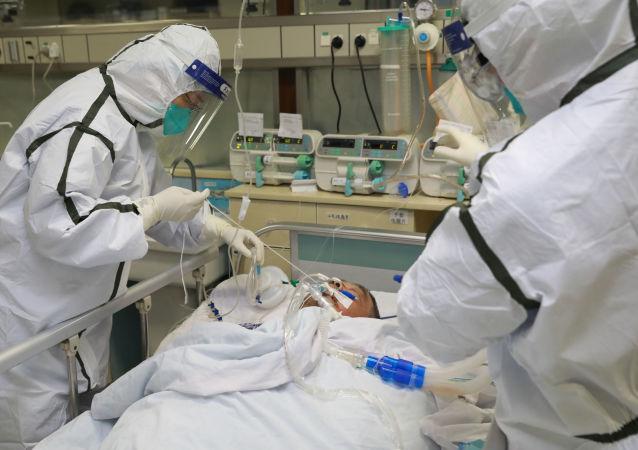 Pracownicy służby zdrowia w kombinezonach ochronnych nad pacjentem z wykrytym koronawirusem