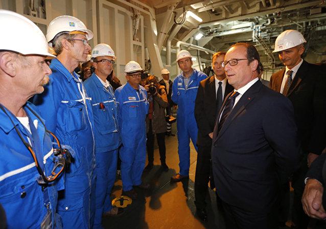 Prezydent Francji Francois Hollande rozmawia z pracownikami na pokładzie Mistrala podczas wizyty w stoczni w Saint-Nazaire we Francji