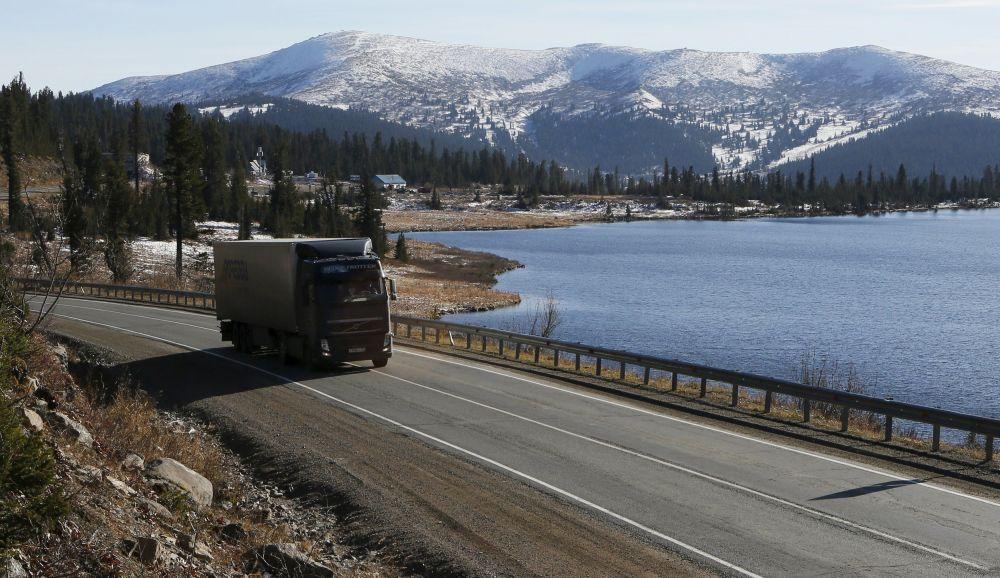 Ciężarówka jedzie wzdłuż szosy Jenisiej M54 wzdłuż jeziora w Sajanach