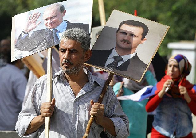 Syryjczyk niesie portrety al-Asada i Putina