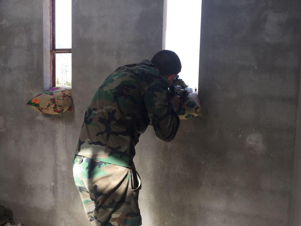 Syryjski żołnierz prowadzi ogień po pozycjach bojowników