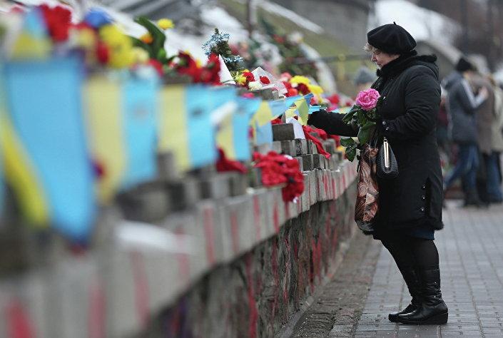 Kobieta składa kwiaty pod pomnikiem upamiętniającym ofiary protestów na Majdanie, do których doszło rok temu w Kijowie