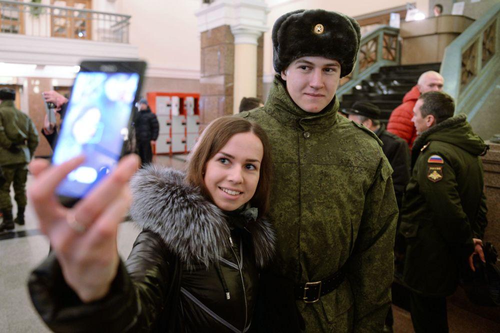 Poborowy z obwodu nowosybiryjskiego robi zdjęcie z dziewczyną na dworcu kolejowym przed odjazdem