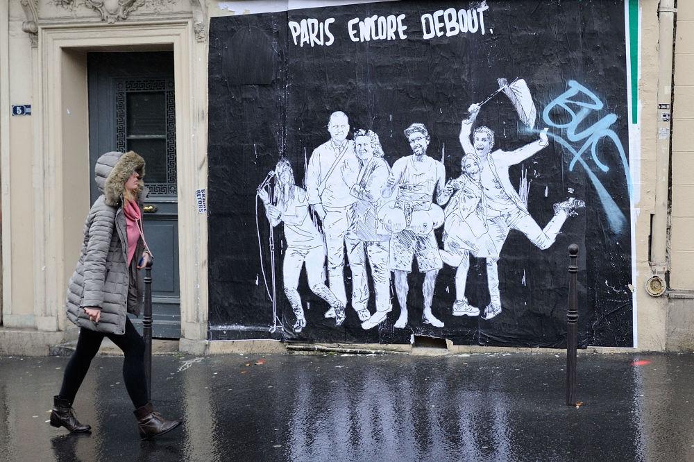 Dziewczyna przy plakacie wspierającym Francuzów po zamachach w Paryżu