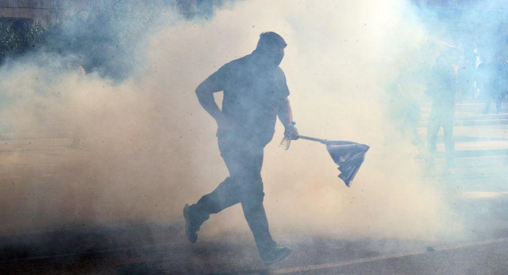 Uczestnik protestów w Atenach biegnie z flagą przez opary gazu łzawiącego