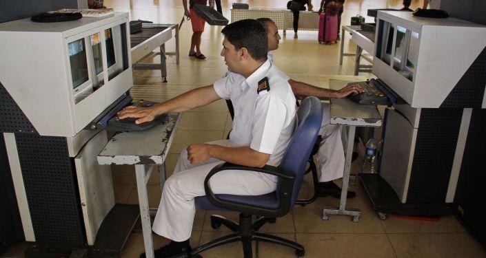 Pracownicy służby bezpieczeństwa egipskiego lotnictwa Szarm el-Szejk skanują bagaż