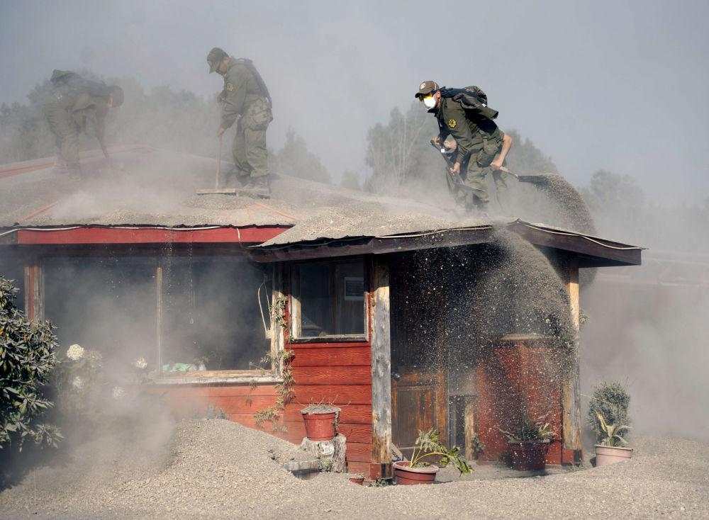 Policjanci czyszczą dom, pokruty popiołem z wulkanu Calbuco w Chile