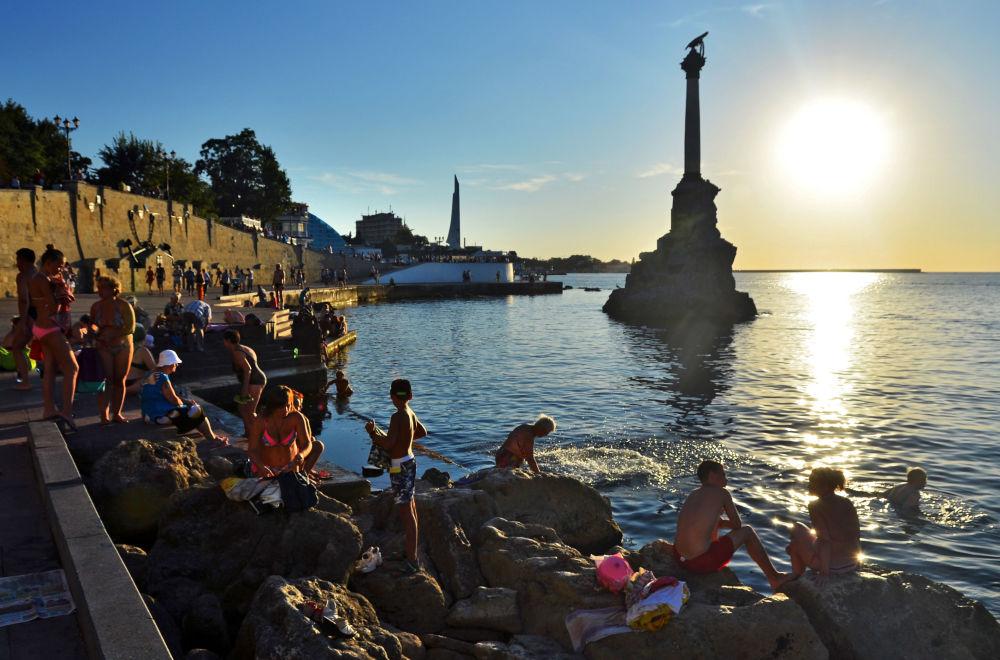 Turyści i mieszkańcy miasta przy pomniku zatopionych statków w Sewastopolu