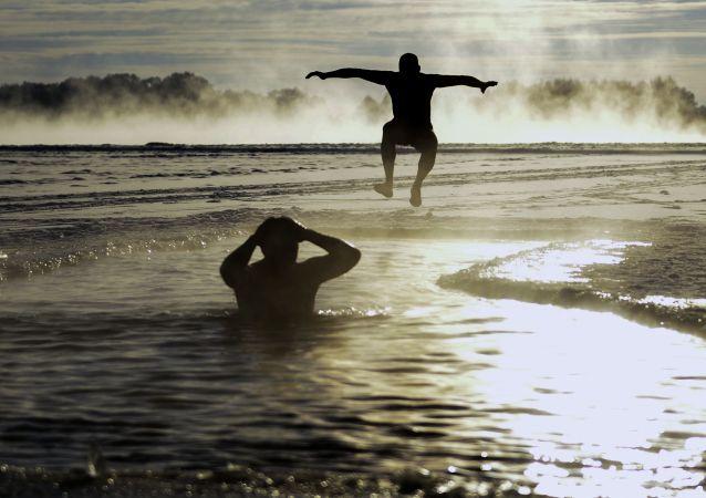Uczestnicy nowogrodzkiego klubu miłośników zimnych kąpieli kąpią się w rzece